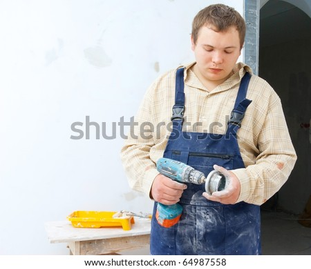 tired worker with mobile drill in hand. House improvement theme - stock photo