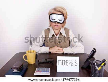 "Tired working girl in a sling eyes sleeps on the desktop labelled ""break"" in Russian"