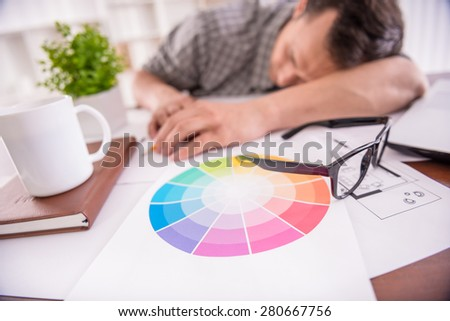 Tired working man sleeping at the workplace full of sketches. - stock photo