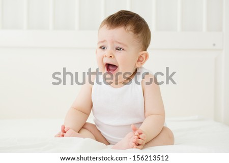 Tired, yawning baby wants to sleep. In bed, indoors shot. - stock photo