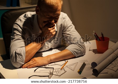 Tired young architect late at work in his office - stock photo