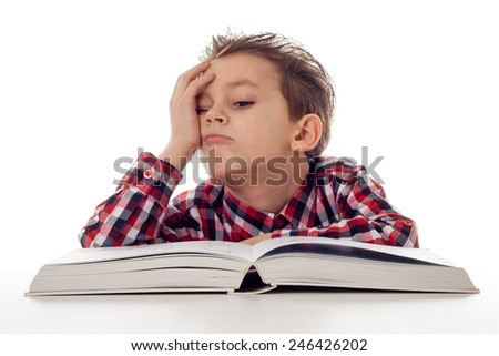 tired young boy in shirt with a big book - stock photo