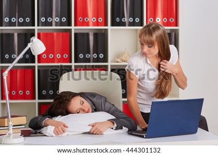 Tired young business woman is sleeping on workplace in the office, another employee took advantage of the situation and is stealing private information from computer of competitor. - stock photo