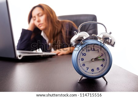 Tired young business woman sleeping next to his laptop computer at the desk, isolated on white - stock photo