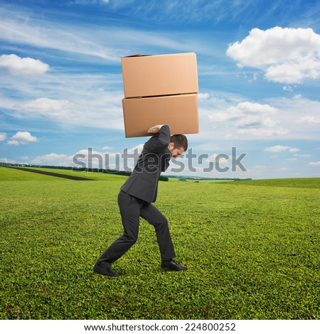 tired young businessman carrying two heavy boxes at outdoor - stock photo