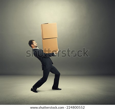 tired young businessman carrying two heavy boxes over grey background