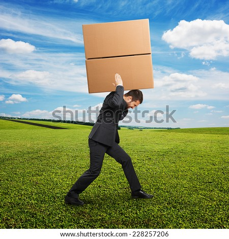 tired young businessman in suit carrying two heavy boxes at outdoor - stock photo