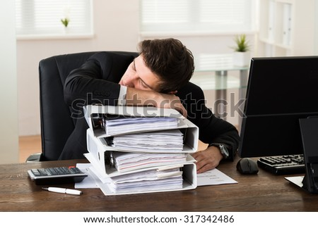 Tired Young Businessman Sleeping On Stack Of Binders At Desk - stock photo