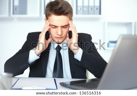 Tired young businessman with problems and stress at his workplace in bright office - stock photo