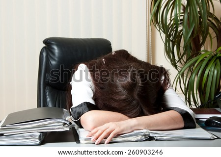 Tired young businesswoman sleeping in her office sitting at her desk - stock photo