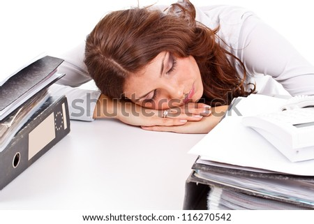 Tired young businesswoman sleeping on the table - stock photo