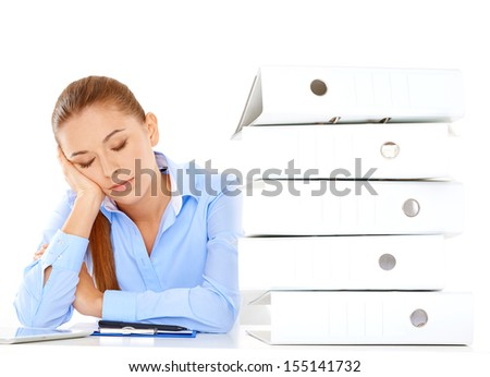 Tired young businesswoman taking a nap at her desk during her lunch break resting her head on her hand alongside a tall stack of office files - stock photo