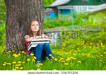 Tired young girl in the park with books.