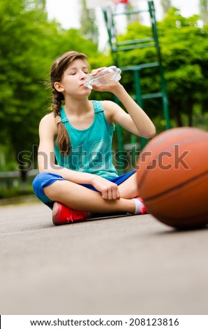 Tired young girl thirsty from playing basketball drinking water - stock photo
