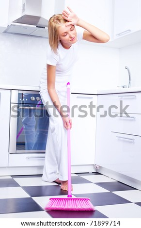 tired young housewife with a broom in the kitchen - stock photo