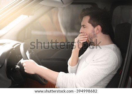 Tired young man driving his car. - stock photo
