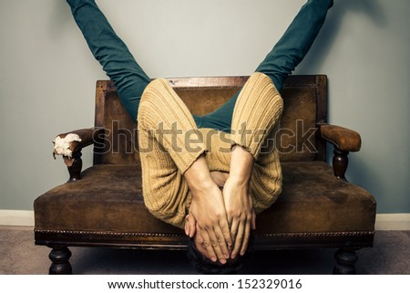 Tired young man is upside down on old sofa - stock photo
