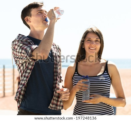 Tired young travelers having a rest and drinking cold water outdoor - stock photo