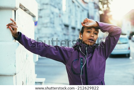 Tired young woman catching breath after training in city - stock photo