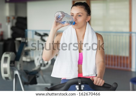 Tired young woman drinking water while working out at exercise bike in gym - stock photo
