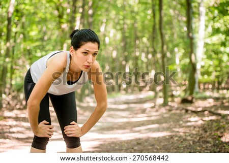 Tired young woman resting after jogging in nature - stock photo