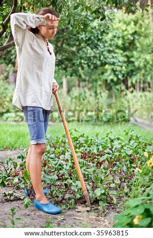Tired young woman with hoe working in the garden bed - stock photo