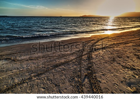 tires track on the sand at sunset - stock photo
