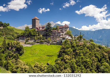 Tirol castle on a sunny summer day with blue sky, white clouds, green meadows and trees - stock photo