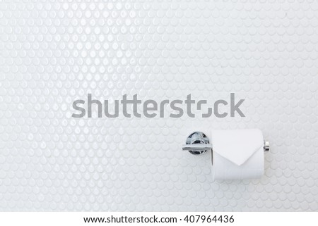 Tissue papar roll on white wall background in toilet - stock photo