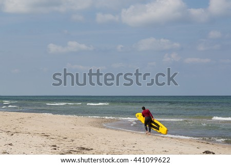 Tisvilde, Denmark - June 20, 2016: A female Lifeguard with her surf board at Tisvilde beach.