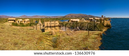 Titicaca lake Peru Uro huts on floating island PANORAMA - stock photo