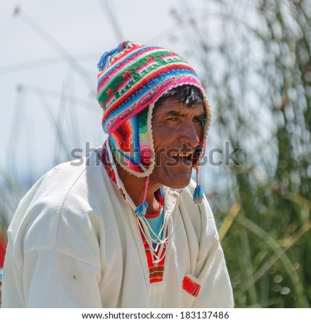 TITICACA, PERU - JAN 03, 2014: Unidentified indian men welcome tourists on a reed island Uros in Lake Titicaca. The Qhichwa Uros are a pre-Incan people who live on 42 self-fashioned floating islands