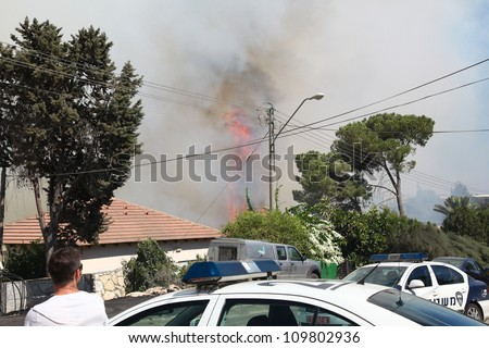 TIVON, ISRAEL - AUGUST 09: Fire erupts above the streets after a forest fire breaks out in Kiryat Tivon. Rescue workers struggle to prevent further damage. Tivon, Israel August 09, 2012 - stock photo
