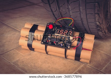 TNT time bomb near wheel of car ( Filtered image processed vintage effect. ) - stock photo