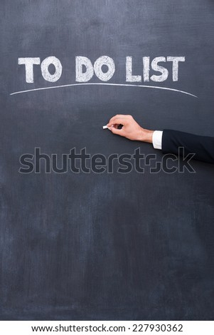To do list. Close-up of human hand writing to do list on the blackboard  - stock photo