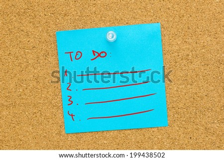 To do list on blue post it paper pinned on a cork bulletin board. - stock photo