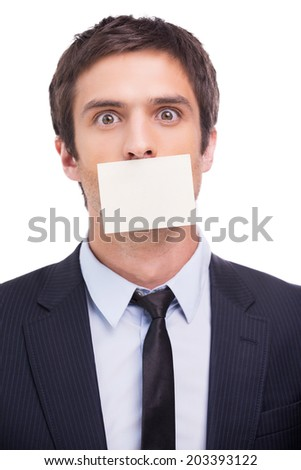 To do list. Portrait of frustrated young man in formalwear and adhesive note on his mouth standing against white background and looking at camera - stock photo