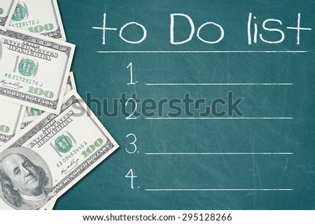 TO DO LIST text written on a green chalkboard with a number of one hundred US dollar notes  - stock photo