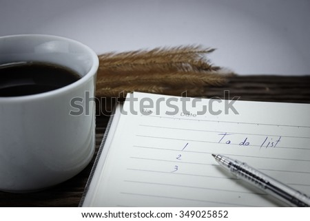 To do list  with a pen and cup of fresh coffee