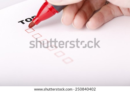 To Do list with check marks isolated on white - women hand with red marker - stock photo
