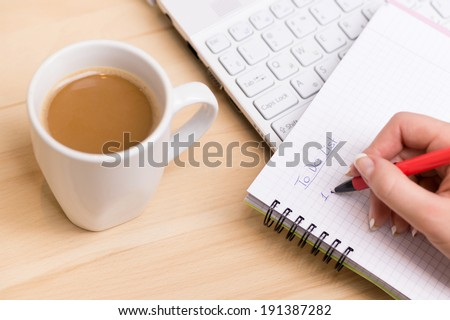 To do list. Woman writing a 'to do list' at her desk with a cup of fresh coffee - stock photo