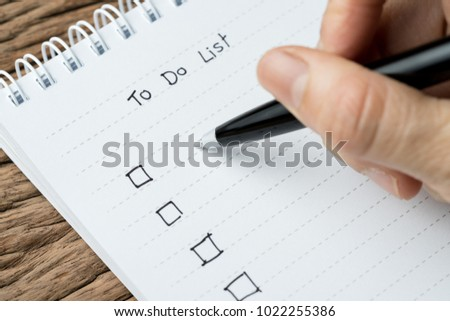 To do lists, finish work, tasks priority concept, closed up of hand holding pen writing list on white paper notepad on wood table in soft tone.