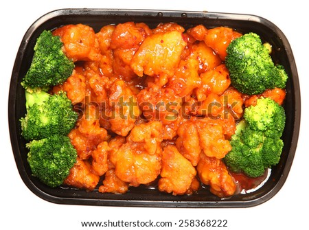 To go or delivery container of general tso chicken and broccoli. Top view over white. - stock photo