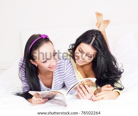 to happy girls reading a magazine on the bed at home - stock photo