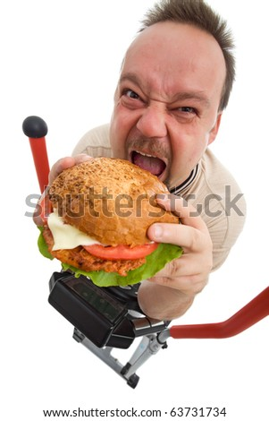 To hell with exercises - man eating big hamburger on elliptical trainer device - isolated