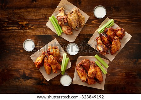 to pdown view of chicken wing party platter made to share with four different flavors and ranch dipping sauce - stock photo