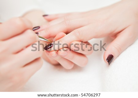 To the girl do manicure in salon close up