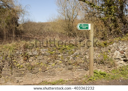 To Unmetalled Road.  An amusing county sign that actually shows you, importantly, the way to a dirt track, stands beside an old stone fence covered in small cold weather plants - stock photo