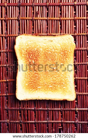 Toast bread on wicker wooden background top view - stock photo