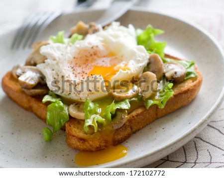 Toast sandwich with mushroom, poached egg and lettuce, selective focus - stock photo